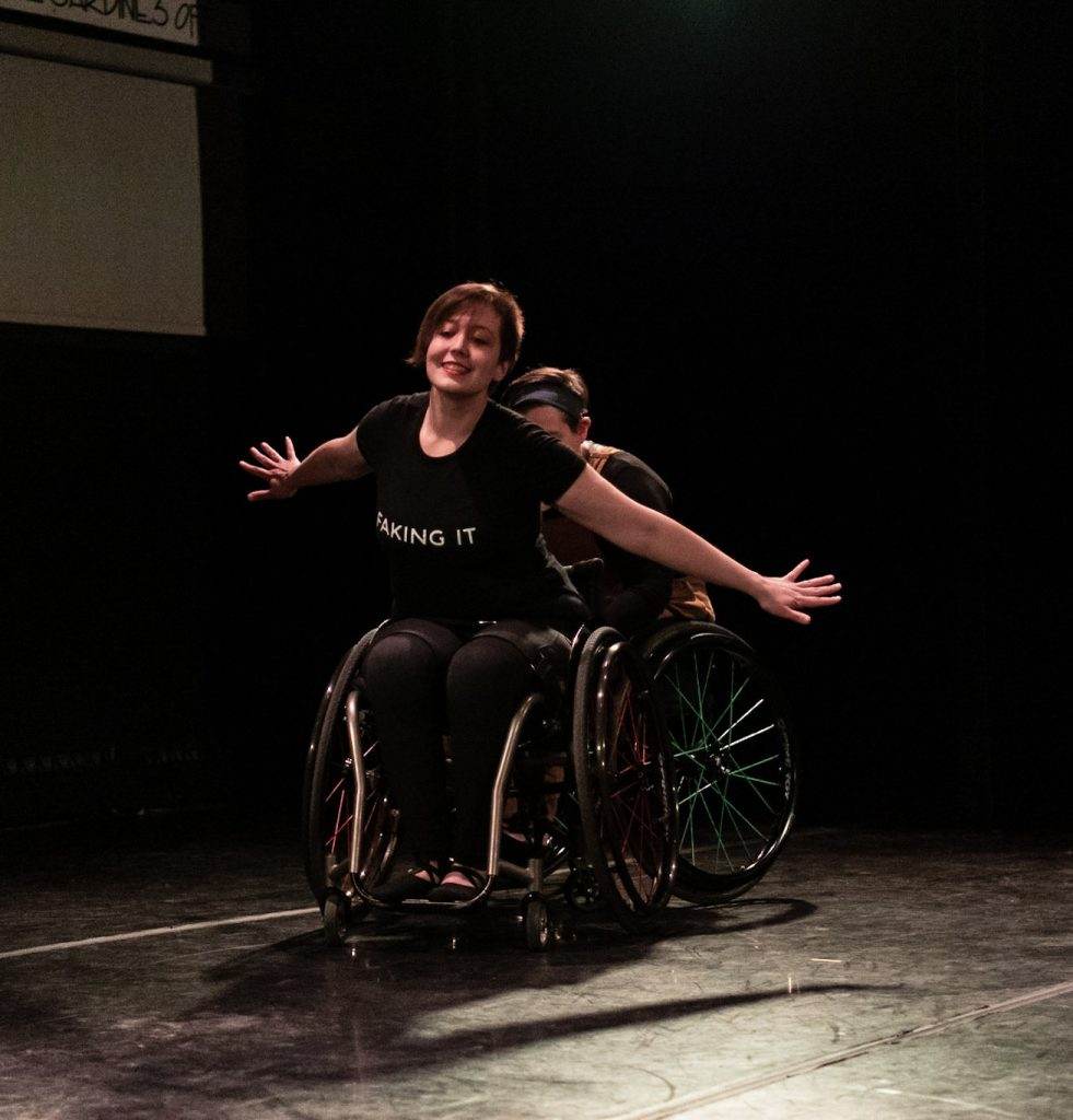 Shay And Jen are on a stage. Shay is behind Jen and only partially visible, pushing their wheelchair from behind. Jen's arms are down and stretched out at their sides while being propelled forward. Jen has an excited and apprehensive look on their face. Jen is wearing a black T-shirt that says Faking it.