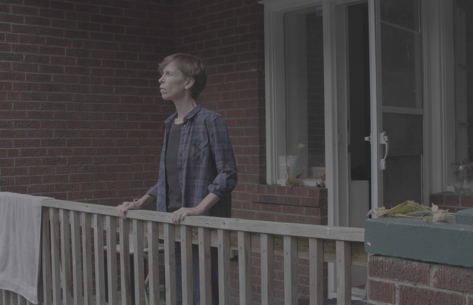 A photograph of Alex standing on her apartment balcony.  She is a white woman wearing a purple and blue plaid shirt over a black t-shirt and blue jeans. The balcony door is ajar. She faces out at the edge of it, and holds the wooden railing.